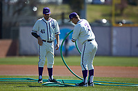 Garrett Letchworth (7) and Kirby Osborn (41) of the High Point Panthers wrap up the hose after watering the infield prior to the game against the NJIT Highlanders at Williard Stadium on February 19, 2017 in High Point, North Carolina. The Panthers defeated the Highlanders 6-5. (Brian Westerholt/Four Seam Images)