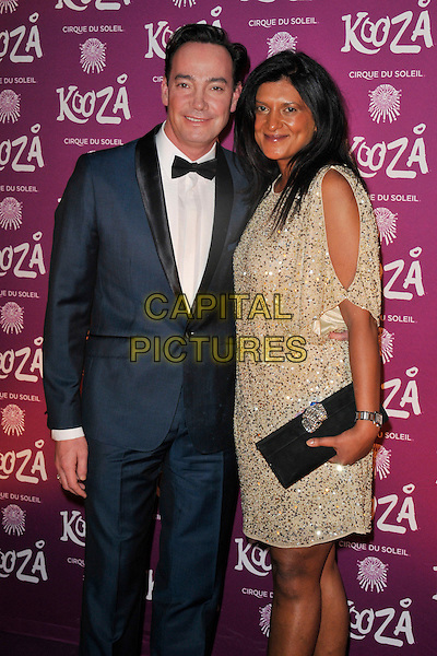 Craig Revel Horwood & guest.Opening night of  the Cirque du Soleil's 'Kooza' at the Royal Albert Hall, London, England..8th January 2013 .half length tuxedo gold dress clutch bag black blue white bow tie.CAP/WIZ.© Wizard/Capital Pictures.
