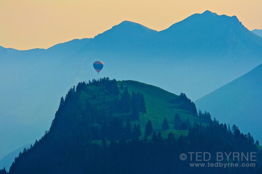 Hot air balloon coming over a ridge in an Alps sunrise