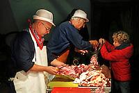 Nederland Arnhem 2015. Slachtdag in het Nederlands Openluchtmuseum. Twee scharrelvarkens, die een jaar gescharreld hebben in het museum, zijn geslacht in een slachterij. Tijdens Slachtdag worden de varkens verwerkt door drie slagers. Kind helpt met de gehaktmolen. Foto Berlinda van Dam / Nederlandse hoogte