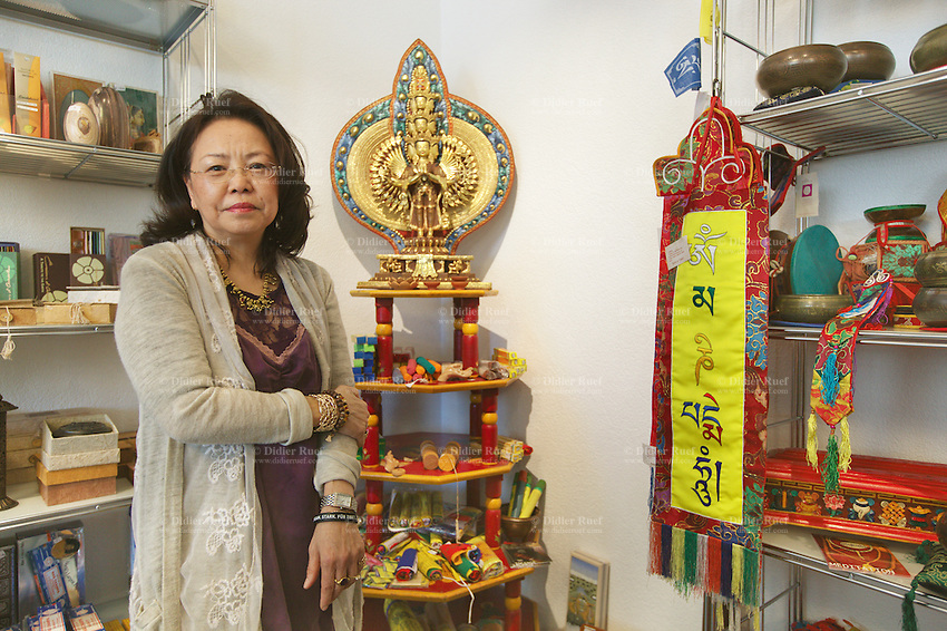 "Switzerland. Canton Aargau. Brugg. Yangchen Büchli in her showroom ""Pema of Tibet"". She stands close to a statue of Chenresi, the Bodhisattva of compassion who is also the protective deity of Tibet. The swiss tibetan woman is an Aeschimann's child who arrived 50 years ago in Switzerland to receive custody on a private initiative by an influential Swiss industrialist, Charles Aeschimann. In 1962, Charles Aeschimann agreed with the Dalai Lama to take 200 children and place them in Swiss foster homes and give them a chance for a better life and a good education. Most of the children still had parents in exile or in Tibet, just a few were orphans. 25.02.2015 © 2015 Didier Ruef"