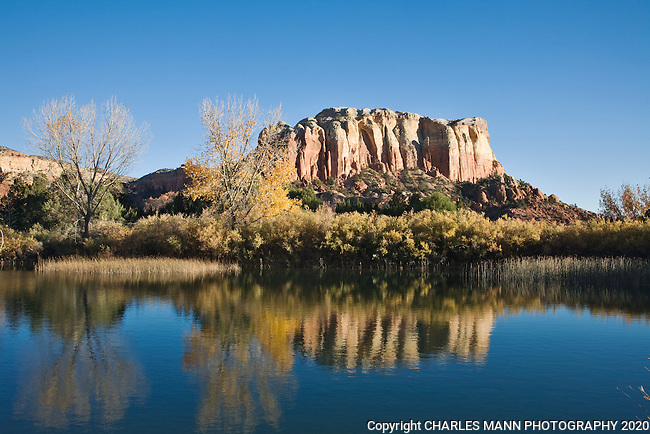 The reflection of Kitchem Mesa is seen in the still water of a small pond on an autumn day at Ghost Ranch, a resort and conference center near the small village of Abiquiu in northern New MExico
