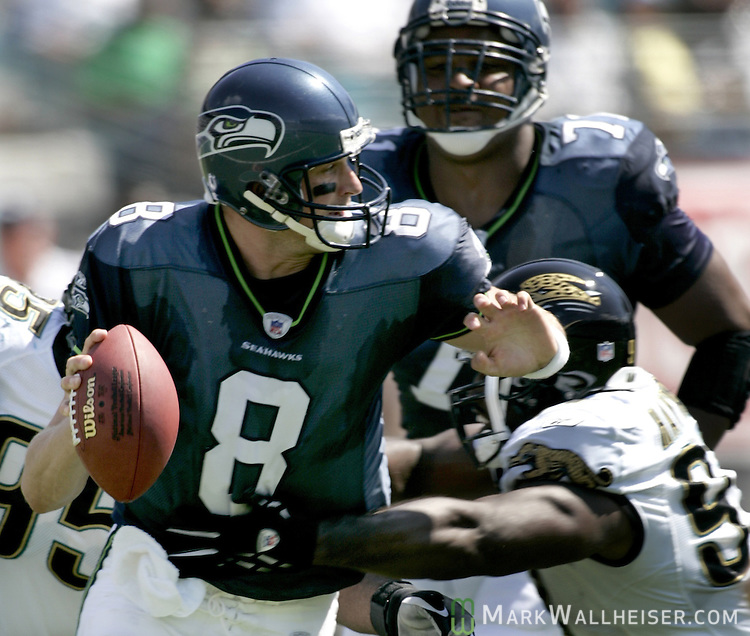 Seattle Seahawks quarterback Matt Hasselbeck (L) is pressured by the Jacksonville Jaguars' defensive end Reggie Hayward (R) during the Jaguars' 26-14 win over the Seahawks in Jacksonville, Florida September 11, 2005. Behind right is the Seahawks' tackle Walter Jones.