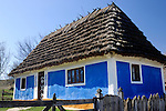 Ancient country house with thatched roof in Pirogovo, Ukraine, Eastern Europe.
