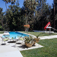 Bertoia chairs surround a low table by the pool and there is a large metal sculpture on the lawn