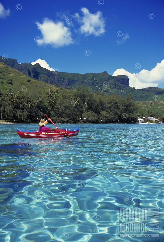 Kayaker paddles in waters off Moorea, French Polynesia Tahiti