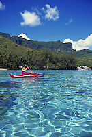 Kayaker paddles in waters off Moorea, French Polynesia Tahiti