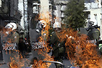 Pictured: Riot police as seen through flames  Friday 12 February 2016<br /> Re: Violent clashes between farmers and riot police outside the Ministry of Agricultural Development in Athens, Greece. The farmers travelled from Crete to protest against pension and welfrae reforms proposed by the Greek government,