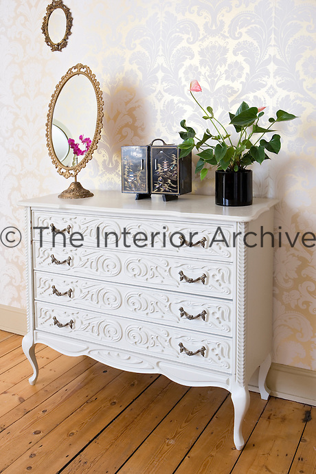 In the master bedroom the carving on the front of a vintage chest-of-drawers echoes the swirling pattern of pale pink wallpaper on the wall behind