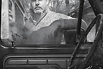 A Mechanic with a handlebar mustache looking through the window of a truck