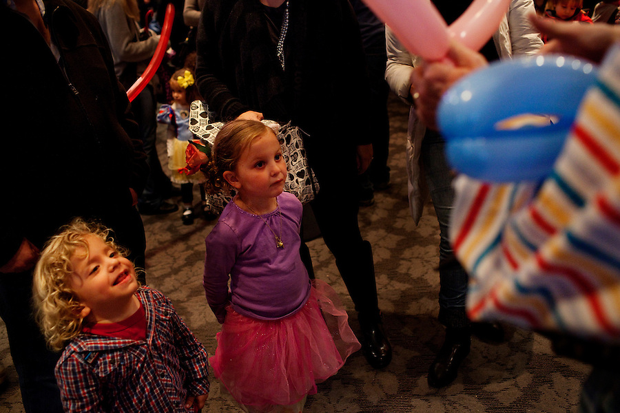 Los Angeles, California, March 20, 2011 - Children watch a clown create balloon sculptures during a Purim carnival at Stephen S. Wise Temple. The temple is a reform synagogue with a strong Persian congregation...Purim is a Jewish holiday that commemorates the deliverance of the Jewish people living in the Persian Empire from genocide at the hands of the political advisor, Haman, to the Persian King Ahasuerus, as documented in the Talmud's Book of Esther. It is celebrated by the reading of the Scroll of Esther or the Megillah, sending food gifts to friends, giving charity to the poor and celebrating with a festive meal. During the reading of the Megillah, when Haman's name is mentioned (which happens 54 times) the congregation engages in loud roars and the use of rattles in an effort to blot out his name. Today children and some adults dress in costume and masquerade to celebrate Purim. The custom is believed to have originated during the 15th century by Italian Jews influenced by the Roman carnival. One idea for the costumes is that God disguised his presence behind many of the natural events that happened during Purim. ..Nowruz, the Persian New Year, marks the first day of spring and the beginning of the Persian calendar. It is marked by Haft Sin, or the seven S's, which include sabzeh (wheat, barley or lentil sprouts growing in a dish - symbolizing rebirth); samanu (a sweet pudding made from wheat germ -symbolizing affluence); senjed (the dried fruit of the oleaster tree - symbolizing love); s?r (garlic - symbolizing medicine); s?b (apples - symbolizing beauty and health); somaq (sumac berries - symbolizing the sunrise); serkeh (vinegar - symbolizing age and patience). Each of these items are laid on a table in the home. Other items include decorated eggs, symbolizing fertility, a mirror symbolizing cleanliness and honesty and a bowl with goldfish, symbolizing life within life. .