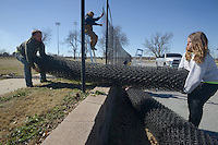 NWA Democrat-Gazette/BEN GOFF @NWABENGOFF<br /> Hunter Horn (left) and Nathan Purcell with Carnahan-White Fence Company in Springdale bring in a roll of chain-link fabric Thursday, March 3, 2017, while replacing the fence around the soccer fields at Memorial Park in Bentonville. The crew was replacing streched out 11.5 gauge fabric with sturdier 8 gauge fabric.