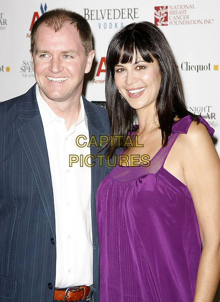 "ADAM BEASON & CATHERINE BELL.Super Bowl XLII ""Saturday Night Spectacular"" Presented By American Airlines and Celebrity Investments To Benefit National Breast Cancer Foundation and The Marshall Faulk Foundation, Phoenix, Arizona, USA..February 2nd, 2008.half length purple dress blue grey gray suit jacket white shirt.CAP/ADM/MJT.©MJT/AdMedia/Capital Pictures."
