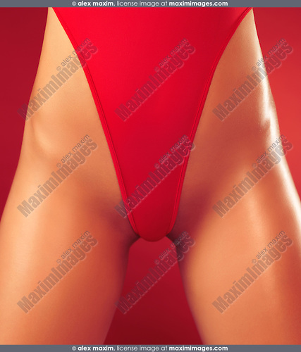 Closeup of a sexy young woman with tanned body in red high-cut double dip swimsuit on red background