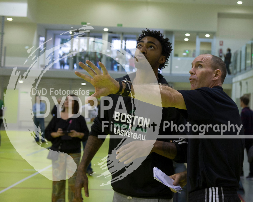 Coach Neal Meyer talks with James Young during clinic with kids