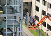NWA Democrat-Gazette/MICHAEL WOODS &bull; @NWAMICHAELW<br /> Jason Simpson (from left) and James Meeks, with Architectural Products Inc. in Little Rock, guide a piece of glass into place Thursday August 6, 2015, while working on the Northwest stairwell of the Stadium Drive Parking Garage on the University of Arkansas campus in Fayetteville.  Crews from API were installing new glass to enclose each of the stairwells of the garage.