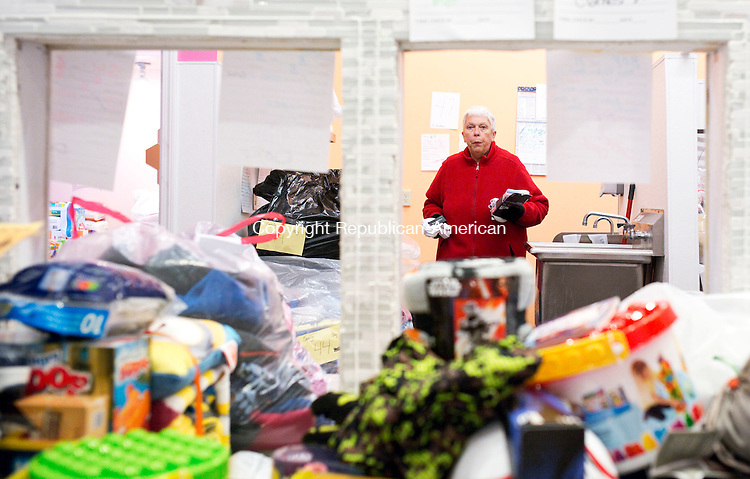 Southbury, CT- 09 December 2015-120915CM02-  Barb Boston of Southbury carries presents in Southbury on Wednesday.   Volunteers with the Southbury Needy Fund were bagging donated gifts for children this Christmas.      Christopher Massa Republican-American