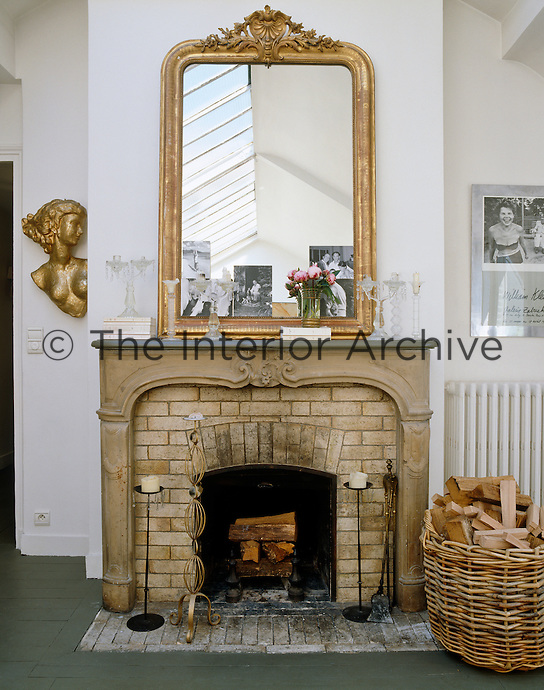 An elegant gilt-framed mirror rests on the mantelpiece of a brick fireplace in this attic living room