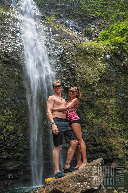 A couple enjoy Hanakapi'ai Falls after hiking to it from a side trail from the Kalalau Trail, Kaua'i.