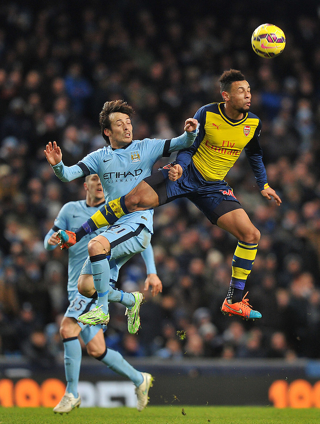 Manchester City's David Silva and Arsenal's Francis Coquelin jump for the ball<br /> <br /> Photographer Dave Howarth/CameraSport<br /> <br /> Football - Barclays Premiership - Manchester City v Arsenal - Sunday 18th January 2015 - Etihad stadium - Manchester<br /> <br /> &copy; CameraSport - 43 Linden Ave. Countesthorpe. Leicester. England. LE8 5PG - Tel: +44 (0) 116 277 4147 - admin@camerasport.com - www.camerasport.com