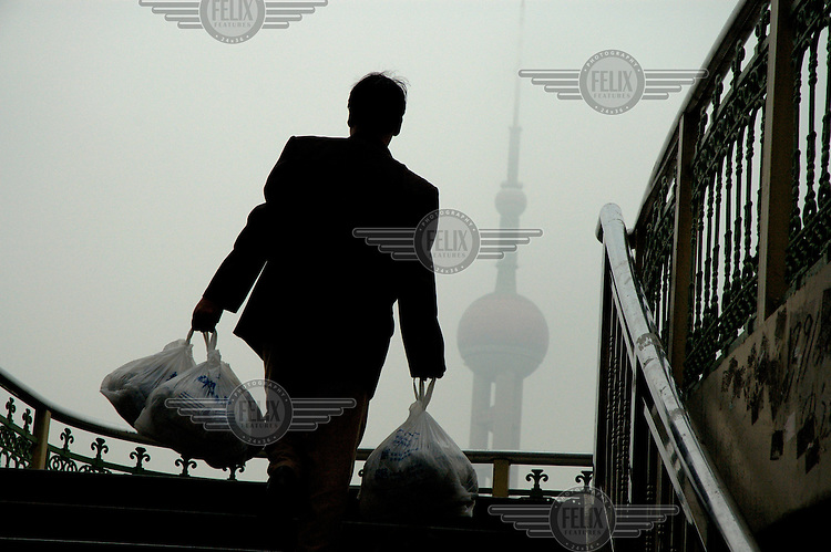 Man with his shopping on a pedestrian overpass, with the Oriental Pearl TV Tower coming out of a grim pollution laden haze behind.