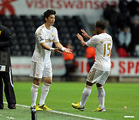 Wednesday, 12 December 2012<br /> Pictured L-R: Ki Sung Yueng of Swansea enters the game as a substitute for team mate Wayne Routledge<br /> Re: Capital One Cup, fifth round, Swansea City FC v Middlesbrough at the Liberty Stadium, south Wales.
