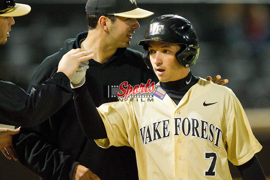 Joey Rodriguez (7) of the Wake Forest Demon Deacons high fives teammates after scoring a run in the 8th inning against the North Carolina State Wolfpack at Wake Forest Baseball Park on March 15, 2013 in Winston-Salem, North Carolina.  The Wolfpack defeated the Demon Deacons 12-6.  (Brian Westerholt/Sports On Film)