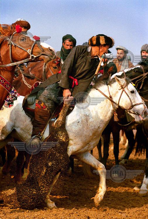 """Afghanistan, dec 2001.Mazar-i-Sharif.In Afghanistan, een land van krijgsheren, is buzkashi de nationale sport..Buzkashi, letterlijk """"grijp het schaap"""" is een ruige sport te paard, waarbij de kunst eruit bestaat om een schape- of kalfskarkas te grijpen en over het veld heen in een ring te slepen..De oorsprong van de sport zou teruggaan tot de tijd van Djenghis Khan, toen het gevecht nog ging om een mensenlichaam..Ook onder de Taliban bleef buzkashi razend populair, hoewel de sport onder zware druk stond van het regime..Enkele weken voorheen namen ruiters en paarden nog deel aan het strijdtoneel op het oorlogsfront, vandaag pakken ze uit met hun moed, durf, handigheid en rijkunst, waarden die traditioneel van levensbelang zijn in een nomadencultuur..Het is ieder voor zich en het gaat er wild aan toe op het veld, er klinken zweepslagen, gebries en gebrul uit de kluwen van paarden en mannen, kwetsuren en breuken horen erbij..De winnaar neemt stijgerend het applaus van het publiek in ontvangst...BUZKASHI..In Afghanistan, a country of warlords, buzkashi is the national sport...Buzkashi, literally Ôgrabbing the dead goatÕ, is a rough sport on horseback. During the game horsemen try to grab the carcass of a calf or goat and drag it over the sportsfield into a circle...The game is said to date from the days of Jenghiz Khan, when human carcasses were used..The Taliban tried to ban buzkashi as un-islamic but the sport remained madly popular...Only weeks before horses and horsemen took part in the combat area of war. Today on the sportsfield they show their courage, strength and skill on horseback, values that are traditionally of vital interest in a nomadic culture..The atmosphere on the field is wild, everyone for himself, lashing of whips, snorting and roaring can be heard from the bunch of crazy horsemen, bruises and broken bones are part of the fun...The winner accepts the applause of the audience on a staggering horse....Foto:©Tim Dirven/hh/panos."""