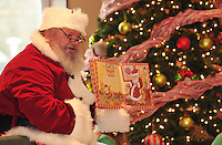 """NWA Media/Michael Woods --12/20/2014-- w @NWAMICHAELW...Santa Clause reads """"The Night Before Christmas"""" to children Saturday morning during the Christmas celebration at the Fayetteville Public Library.  The event gave children a chance to hear Santa Clause read Christmas stories, talk to Santa and have cookies and apple cider with their parents and santas helpers."""