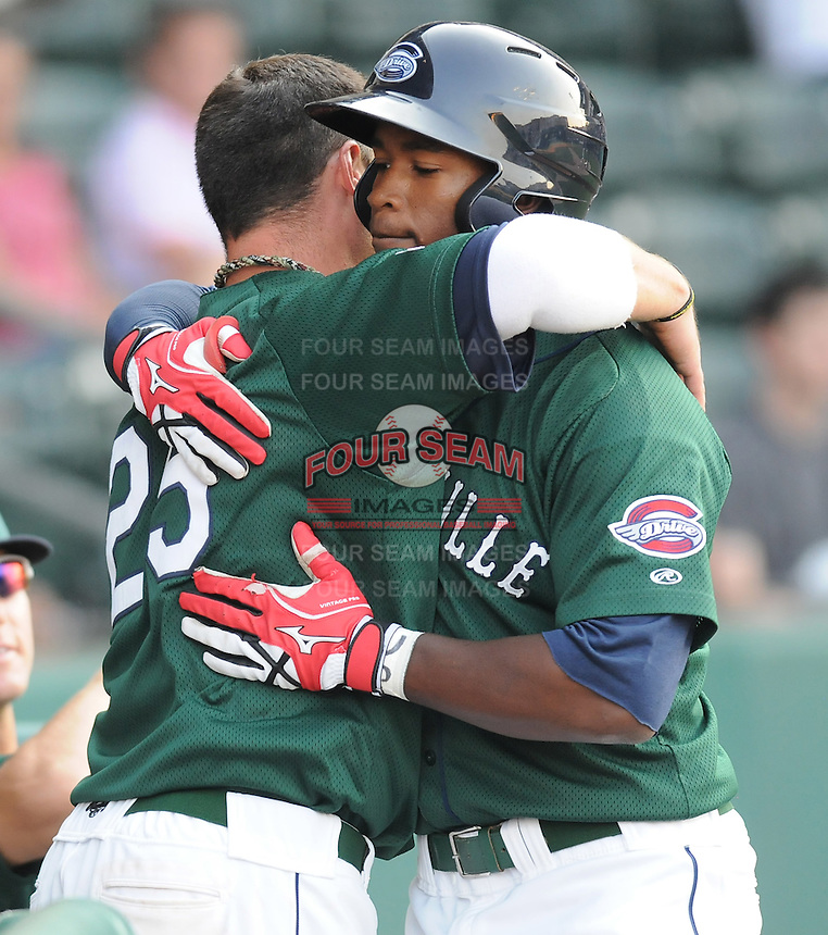Outfielder Brandon Jacobs (24) of the Greenville Drive is congratulated by Bryce Brentz after hitting a home run in a game against the Augusta GreenJackets on April 10, 2011, at Fluor Field at the West End in Greenville, South Carolina. (Tom Priddy / Four Seam Images)