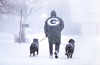A Green Bay Packers fan walking his dogs during a snowstorm in Green Bay, Wisconsin on Christmas Eve day, 1996.