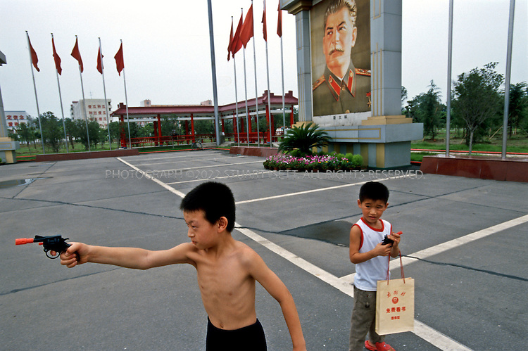 7/15/2005--Nanjie Village, Henan Province, China..A young boy and his brother play with guns in the main square of Nanjie village, a model communist village in the central province of Henan, collectivised its agricultural production and industry in the mid 1980s - when the rest of the country was doing the opposite, introducing market reforms put forward by former leader Deng Xiaoping. ..It continues to be run on Maoist egalitarian lines and has become something of a tourist attraction because of its staunch adherence to the values of the past. ..Photograph By Stuart Isett.All photographs ©2005 Stuart Isett.All rights reserved..Photograph By Stuart Isett.All photographs ©2005 Stuart Isett.All rights reserved.