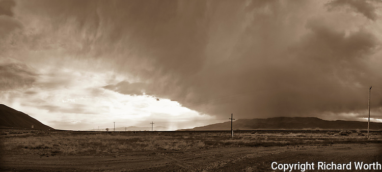 Storm clouds dominate and overwhelm the northern Nevada landscape , except for that far-off, break-of-light.