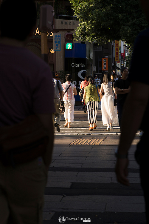 A group of women walking framed by men in shadows in Nagoya Japan.