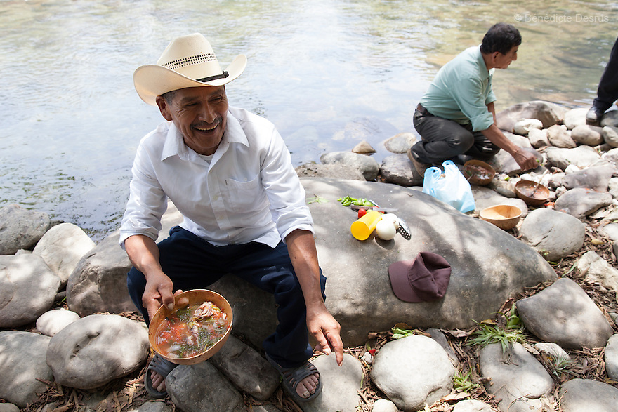 Don Julio eats caldo de piedra with a hand-made corn tortilla on the banks of the Usila River in San Felipe Usila, Mexico on March 30, 2016. Caldo de piedra, or stone soup, is an ancestral dish of the indigenous Chinantec people of San Felipe Usila, a remote village in northern Oaxaca state, Mexico. Traditionally prepared by men in a ritual that dates back to pre-Hispanic times, the soup is cooked in jícara (gourds) by glowing-hot white river rocks that have been heated on a bonfire of orangewood. Ingredients include whole mojarra fish, tomatoes, onion, garlic, chile, epazote, cilantro and fresh water; the soup is seasoned with lime and salt and eaten on the banks of the Usila river. Photo by Bénédicte Desrus