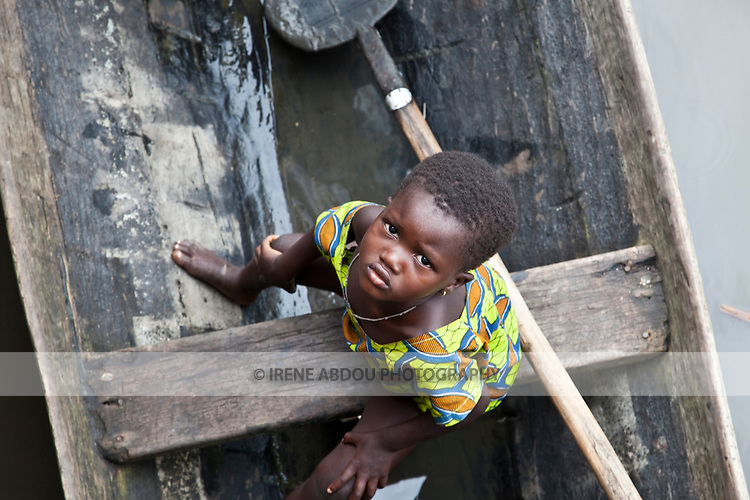 "A young girl in Ganvie sits in a boat, looking up at the camera.  Ganvie, Benin, with some 3,000 stilted buildings and a population of 20,000-30,000 people, may be the largest ""lake vllage"" in Africa.  In Ganvie, the population lives exclusively from fishing, building houses on stilts in and next to Lake Nokoue.  Because the Dan-Homey religion prohibited attacks on communities living in the water, the village of Ganvie dates back to the 16th or 17th century, when it was built to protect people from slavery.  Even Ganvie's fruit and vegetable market is on water!!!"