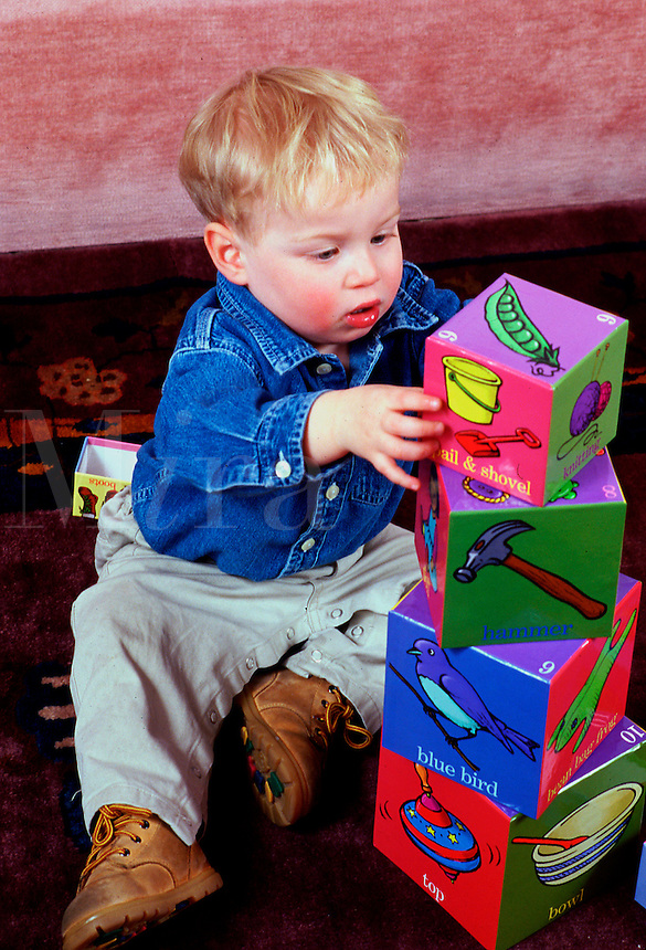 A toddler makes a block tower.