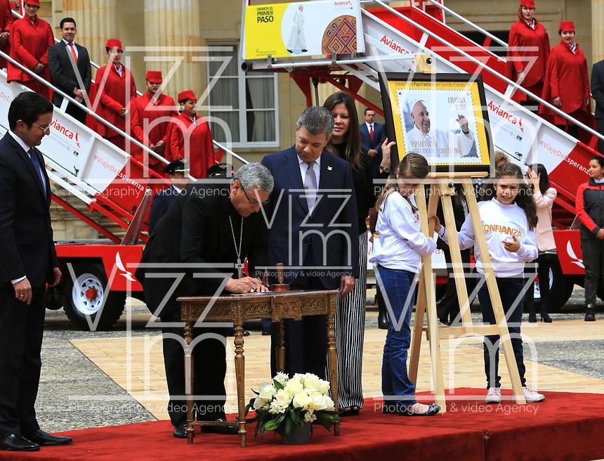 BOGOTÁ - COLOMBIA, 28-08-2017: Juan Manuel Santos, presidente de Colombia, y  monseñor Fabio Suescun Mutis, obispo castrense encargado de la visita del papa, develan la estampilla conmemorativa durante la presentación del papa móvil, la estampilla y la tripulación para la visita del Papa Francisco. El Papa Francisco realiza la visita apostólica a Colombia entre el 6 y el 11 de septiembre de 2017 llevando su mensaje de paz y reconciliación por 4 ciudades: Bogotá, Villavicencio, Medellín y Cartagena. / Juan Manuel Santos, president of Colombia, and Monseñor, Fabio Suescun Mutis, military bishop in charge of the visit of the Pope, reveal the conmemorative stamp during the launch of the Popemovil, stamp and crew to the visit of the Pope Francisco. Pope Francisco made the apostolic visit to Colombia between September 6 and 11, 2017, bringing his message of peace and reconciliation to 4 cities: Bogota, Villavicencio, Medellin and Cartagena Photo: VizzorImage / Jose Miguel Gómez / Prensa Episcopado Colombiano