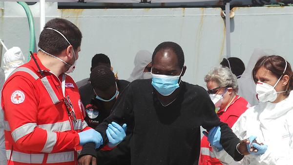 ITA04 BRINDISI (ITALIA) 30/06/2017.- Trabajadores de la Cruz Roja ayudan a desembarcar a los 402 inmigrantes rescatados en el Mediterraáneo a su llegada al puerto de Brindisi (Italia) hoy, 30 de junio de 2017. El primer ministro italiano, Paolo Gentiloni, pidió ayer en Berlín ayuda para hacer frente al drama de los inmigrantes y refugiados y poder mantener la acogida humanitaria de quienes llegan a sus costas, llamamiento ante el que sus socios europeos le prometieron solidaridad. EFE/Max Frigione