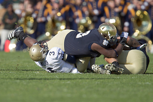 Notre Dame inside linebacker Manti Te'o (#5) and nose guard Louis Nix III (#9) bring down Navy quarterback Trey Miller (#3) during first quarter of NCAA football game between Notre Dame and Navy.  The Notre Dame Fighting Irish defeated the Navy Midshipmen 56-14 in game at Notre Dame Stadium in South Bend, Indiana.