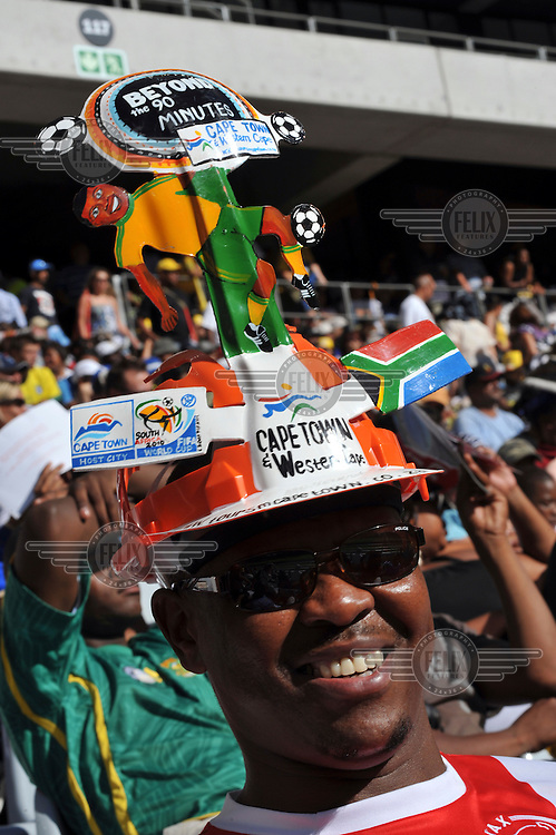 Football fans wearing makarabas (transformed construction hats) at the the official opening of Cape Town's new 2010 FIFA World Cup football stadium. 20,000 fans flocked to the stadium for its first public event since completion in December 2009. The stadium seats 68,000 and the first test event was used to check that all systems, transport, security, staffing and logistics worked satisfactorily.