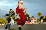 Santa wa;ls past palm trees and folks watching a Christmas concert in the Founders Park ampitheater, Islamorada, Florida Keys