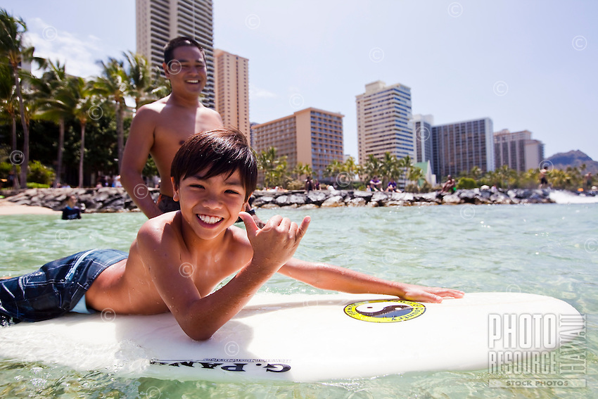 Local boy enjoying a surfing session on a sunny day in Waikiki