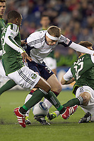 New England Revolution midfielder Zak Boggs (33), in a crowd, thwarted. In a Major League Soccer (MLS) match, the New England Revolution tied the Portland Timbers, 1-1, at Gillette Stadium on April 2, 2011.