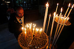 A Christian worshipper lights a candle at the Church of the Nativity, believed to be the birthplace of Jesus Christ, in the West Bank city of Bethlehem, on December 20, 2015. Photo by Wisam Hashlamoun