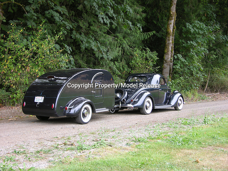 A black tear drop trailer being pulled by a black 1936 Ford.