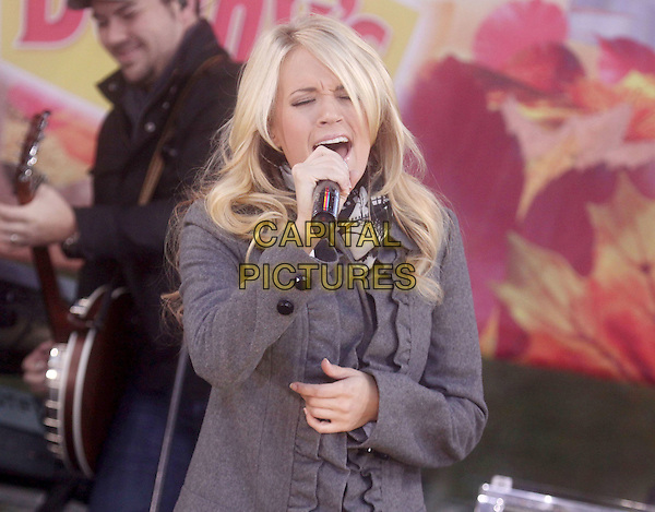 "CARRIE UNDERWOOD.Carrie Underwood performs on ABC's ""Good Morning America"" at the Lincoln Center for the Performing Arts, New York, NY, USA..November 3rd, 2009.stage concert live gig performance performing music half length coat jacket singing mouth open black grey gray ruffle microphone scarf.CAP/ADM/AC.©Alex Cole/AdMedia/Capital Pictures."