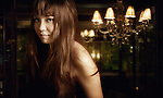 Young asian woman with long brown hair looking at camera with chandelier in background