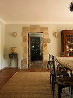 A doorway framed with exposed stonework leads into the breakfast room from the dining area
