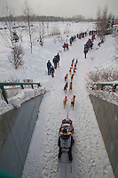 Musher Ed Stielstra emerges from tunnel and passes by spectators at Tudor Road during start of Iditarod 2012, Anchorage, Alaska, March 3, 2012